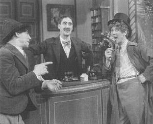 Chico and Groucho engage in some idle banter while watching Harpo eat everything off the hotel reception desk.